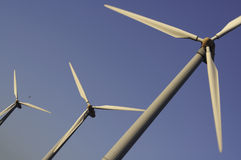 Alternative Energy. 3 windmills on a 45degree angle on a windy day during sunset stock photography