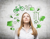 Alternative energy, clean environment. A woman looking up and dreaming, symbols of alternative energy sources painted in green colours on a white poster behind Stock Image