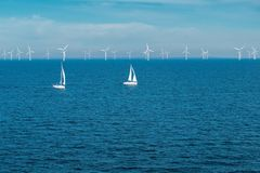 Alternative energy - row of offshore wind turbines and yachts at sea, green energy windmill generators at sea stock images