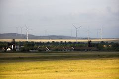 Alternative energy, wind farms stand in the field next to houses. Alternative energy, wind farms stand in the field stock image