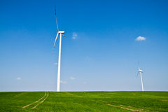 Alternative energy wind turbines and green field Stock Photography