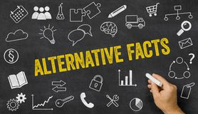 Alternative facts written on a blackboard. With icons stock photo