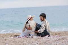 Alternative family with one lady a man and a dog together at the beach enjoying a picnic in friendship and partenership stock photo