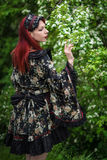 Alternative female model in kimono. Alternative female model with red hair kimono looking over shoulder, trees in background Stock Image