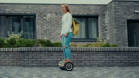 An alternative form of transport for young people. Fashion clothes. Urban people. Modern inhabitant of the big city. Young woman riding on electric scooter. An stock footage