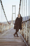Alternative girl in black clothes on old bridge. Alternative girl in black clothes on the old cable bridge Stock Photo
