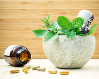 Alternative health care and herbal medicine .Fresh herbs and her. Bal capsule with mortar and pestle on wooden background. Various herbs rosemary ,sage ,sweet stock photo