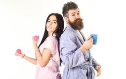 Alternative lifestyle concept. Couple, family on sleepy faces, full of energy. Couple in love in pajama, bathrobe stand. Isolated on white background. Girl with royalty free stock photography