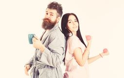 Alternative lifestyle concept. Couple, family on sleepy faces, full of energy. Couple in love in pajama, bathrobe stand. Isolated on white background. Girl with royalty free stock photo