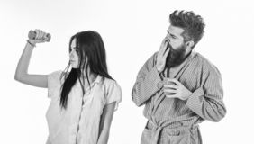 Alternative lifestyle concept. Girl with dumbbell, man with coffee cup. Couple in love in pajama, bathrobe stand. Alternative lifestyle concept. Girl with royalty free stock photography