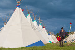 Alternative man next to a row of Tipi tents Stock Images