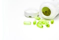 Alternative medicine. Green pills pouring from white bottle Stock Image