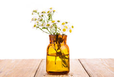 Alternative medicine concept - bottle with camomile on wooden ta Royalty Free Stock Images