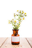 Alternative medicine concept - bottle with camomile on wooden ta Stock Photography
