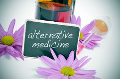 Alternative medicine. A dropper bottle and some flowers with a blackboard label with the text alternative medicine written on it Royalty Free Stock Image