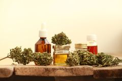Alternative medicine green leaves of medicinal cannabis with extract oil on a wooden table. Alternative medicine green leaves of medicinal cannabis with extract stock photo