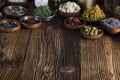 Alternative medicine.  Place for logo and text. Natural medicine background. Brass mortar, bottles and scale. Rustic table. Assorted dry herbs in bowls. Bokeh Stock Photos