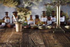 Alternative medicine.  Place for logo and text. Natural medicine background. Brass mortar, bottles and scale. Rustic table. Assorted dry herbs in bowls. Bokeh Royalty Free Stock Image
