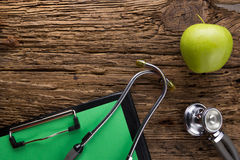 Alternative medicine - stethoscope, clipboard and. Green apple on wood table top view . Medical background. Concept for diet, healthcare, nutrition or medical Royalty Free Stock Photo