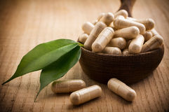 Alternative Medicine. Alternative medicine tablets on a wooden spoon, green leaf royalty free stock photography