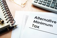Alternative Minimum Tax AMT. Alternative Minimum Tax AMT and  calculator on a desk Stock Photography