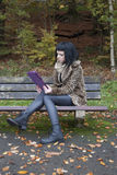 Alternative Model sat on a bench with a tablet PC. In british countryside royalty free stock photos
