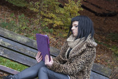 Alternative Model sat on Bench with Tablet PC. In british countryside stock photography