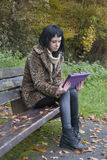 Alternative Model sat on Bench with Tablet PC. In british countryside royalty free stock images