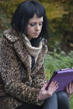 Alternative Model sat on a bench with a tablet PC. In british countryside royalty free stock image
