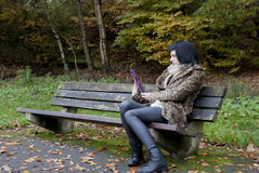 Alternative Model sat on a bench with a tablet PC. In british countryside royalty free stock photo