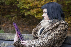 Alternative Model sat on a bench with a tablet PC. In british countryside stock photography
