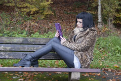 Alternative Model sat on Bench with Tablet PC. In british countryside stock image