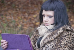 Alternative Model sat on Bench with Tablet PC. In british countryside royalty free stock photography