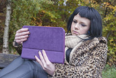 Alternative Model sat on Bench with Tablet PC. In british countryside stock images