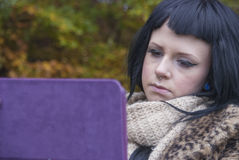 Alternative Model sat on a bench with a tablet PC. In british countryside stock photos