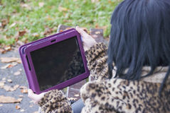 Alternative Model sat on Bench with Tablet PC. In british countryside stock photo