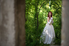 Alternative model in wedding dress. A woman with long red hair, piercings and tattoos walking in the woods wearing a white wedding gown Royalty Free Stock Photos