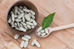 Alternative pills on a wooden spoon and in a bowl, on wooden table Stock Photography