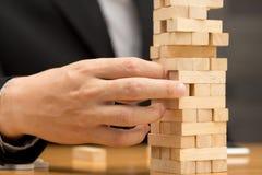 Alternative risk concept. Businessman choosing the wood block Stock Images