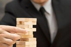 Alternative risk concept. Businessman choosing the wood block Stock Photo