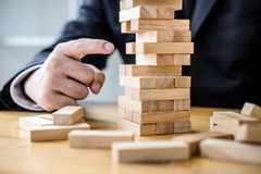 Alternative risk plan and strategy to growth profit in business, Young intelligent businessman playing the wood game, hands of. Executive placing wood block on stock photos