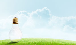 Alternative solar energy concept. Electric light bulb against summer cloudy sky Royalty Free Stock Image