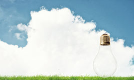 Alternative solar energy concept. Electric light bulb against summer cloudy sky Stock Images