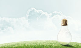 Alternative solar energy concept. Electric light bulb against summer cloudy sky Royalty Free Stock Images