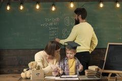 Alternative Studie Mutter unterrichtet klugen Sohn, während Vater auf Tafel auf Hintergrund schreibt Junge, der auf Mutter mit hö lizenzfreies stockbild