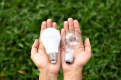 Hands holding LED Bulb and Fluorescent bulb comparing in hands royalty free stock photos