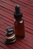 Alternative Therapies. Stone Cairn and a Bottle of Essential Oil on a wooden mat Stock Photo