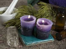 Alternative therapy. Candles, a crystal wand and massage oils Stock Photography