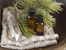 Alternative therapy. Two bottles of massage or essential oil with a crystal point on washcloth with a pine twig Stock Photo