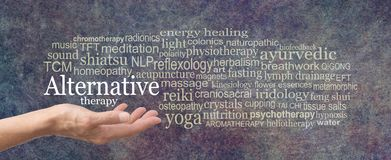Alternative Therapy Word Tag Cloud. Female hand held palm up the words ALTERNATIVE THERAPY in white above surrounded by a relevant word cloud on a rustic dark stock photo